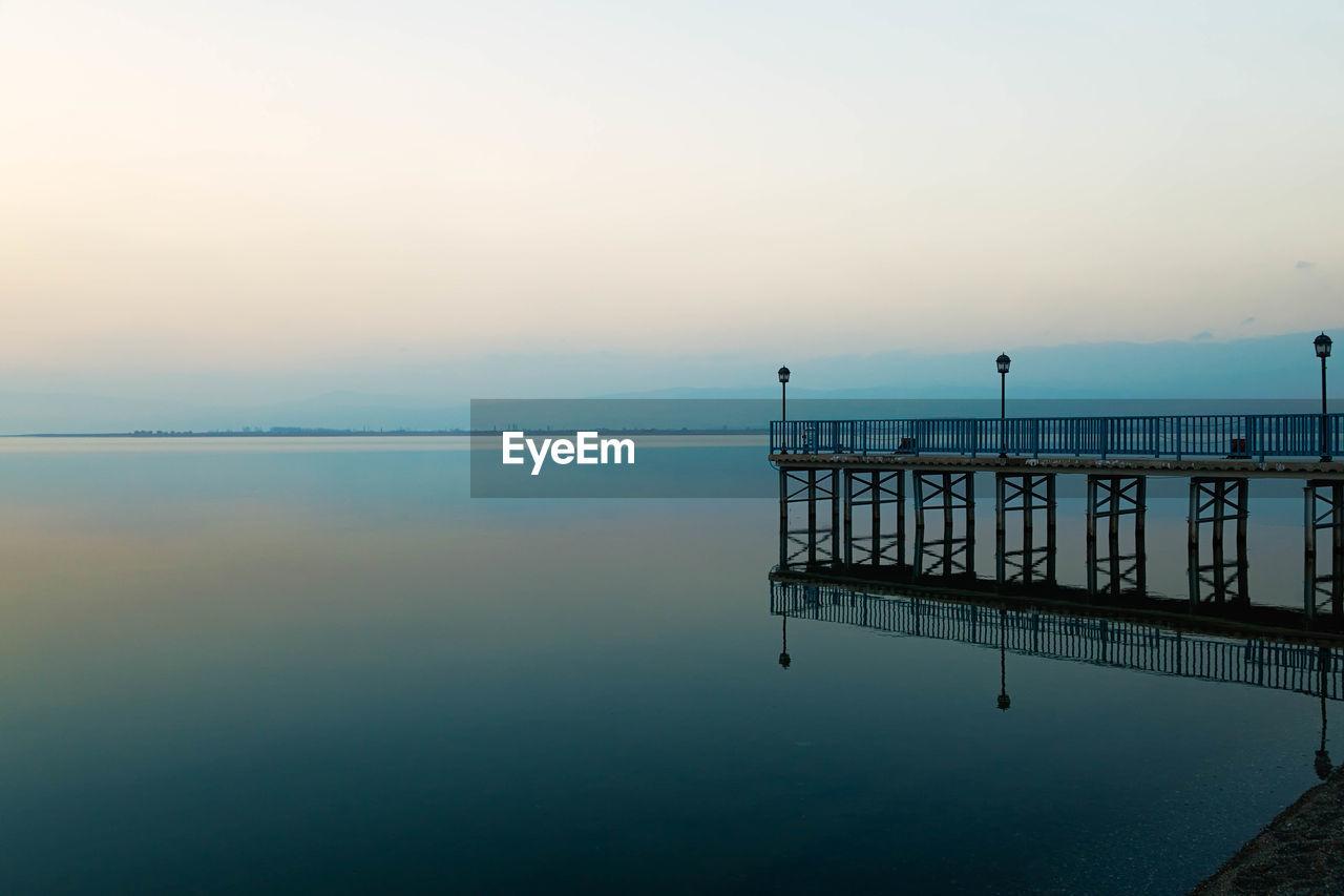 Pier By Calm Lake Against Sky