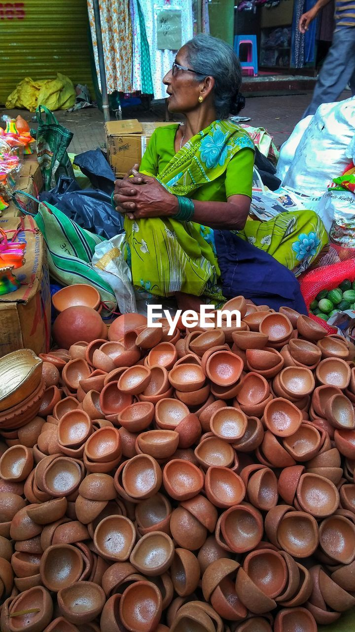 Mature woman selling oil lamp at market