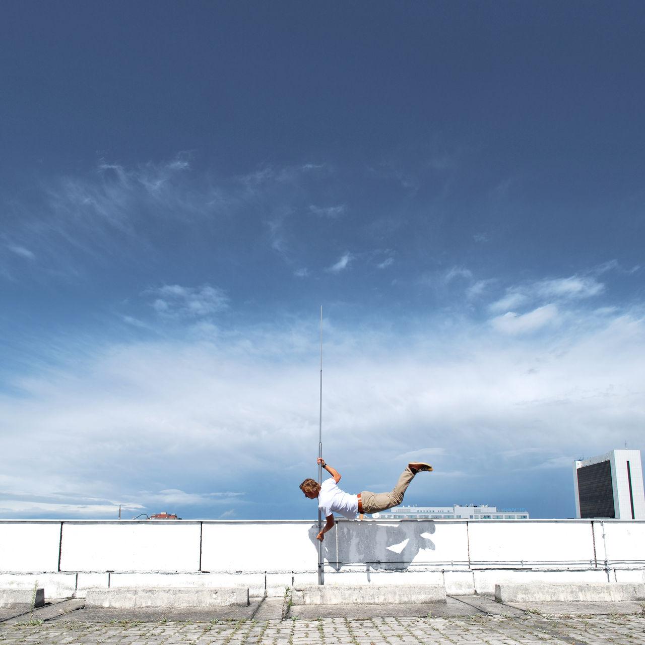 Man Balancing On Pole Against Sky