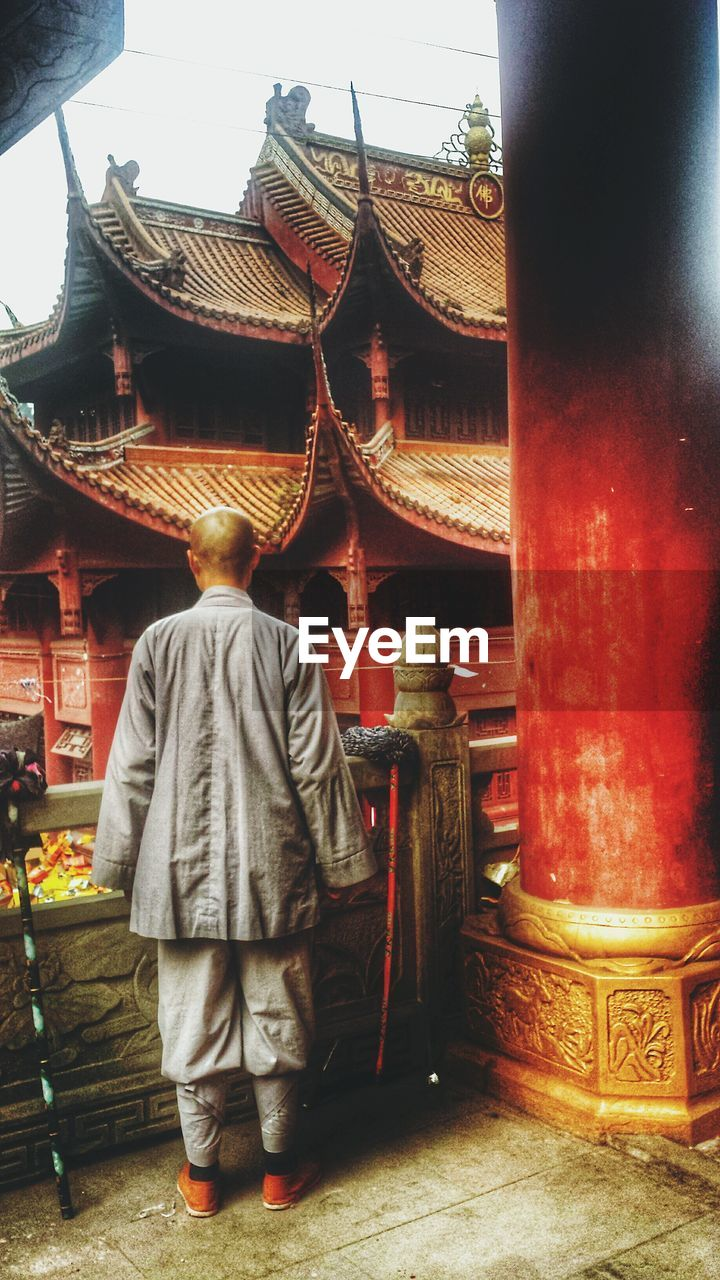 rear view, spirituality, real people, religion, full length, one person, place of worship, men, architecture, lifestyles, traditional clothing, built structure, standing, day, outdoors, hope, people