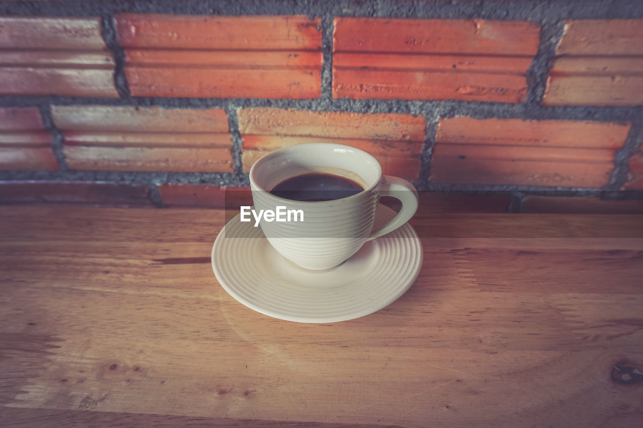 cup, drink, mug, indoors, table, food and drink, still life, refreshment, coffee cup, saucer, crockery, coffee, no people, coffee - drink, high angle view, hot drink, wood - material, tea cup, close-up, tea, place mat