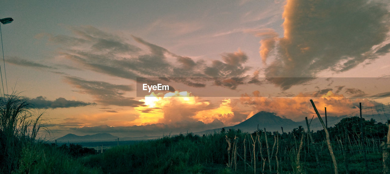sky, cloud - sky, sunset, scenics - nature, beauty in nature, tranquil scene, tranquility, plant, mountain, nature, non-urban scene, no people, environment, landscape, orange color, idyllic, land, field, silhouette, outdoors