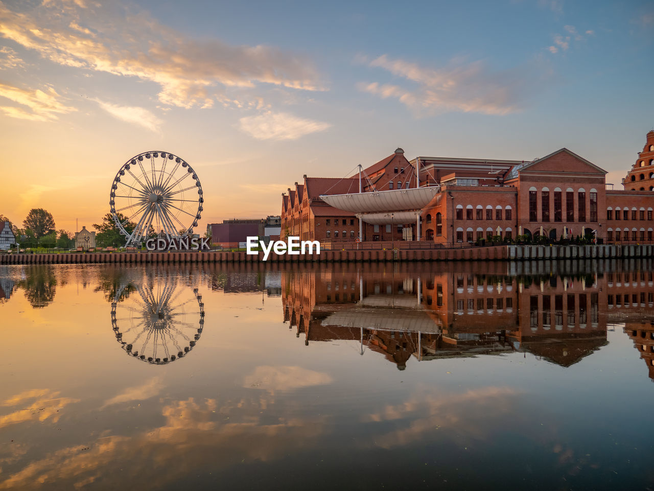 water, sky, built structure, architecture, building exterior, cloud - sky, sunset, reflection, waterfront, nature, ferris wheel, amusement park ride, amusement park, river, building, no people, travel destinations, outdoors