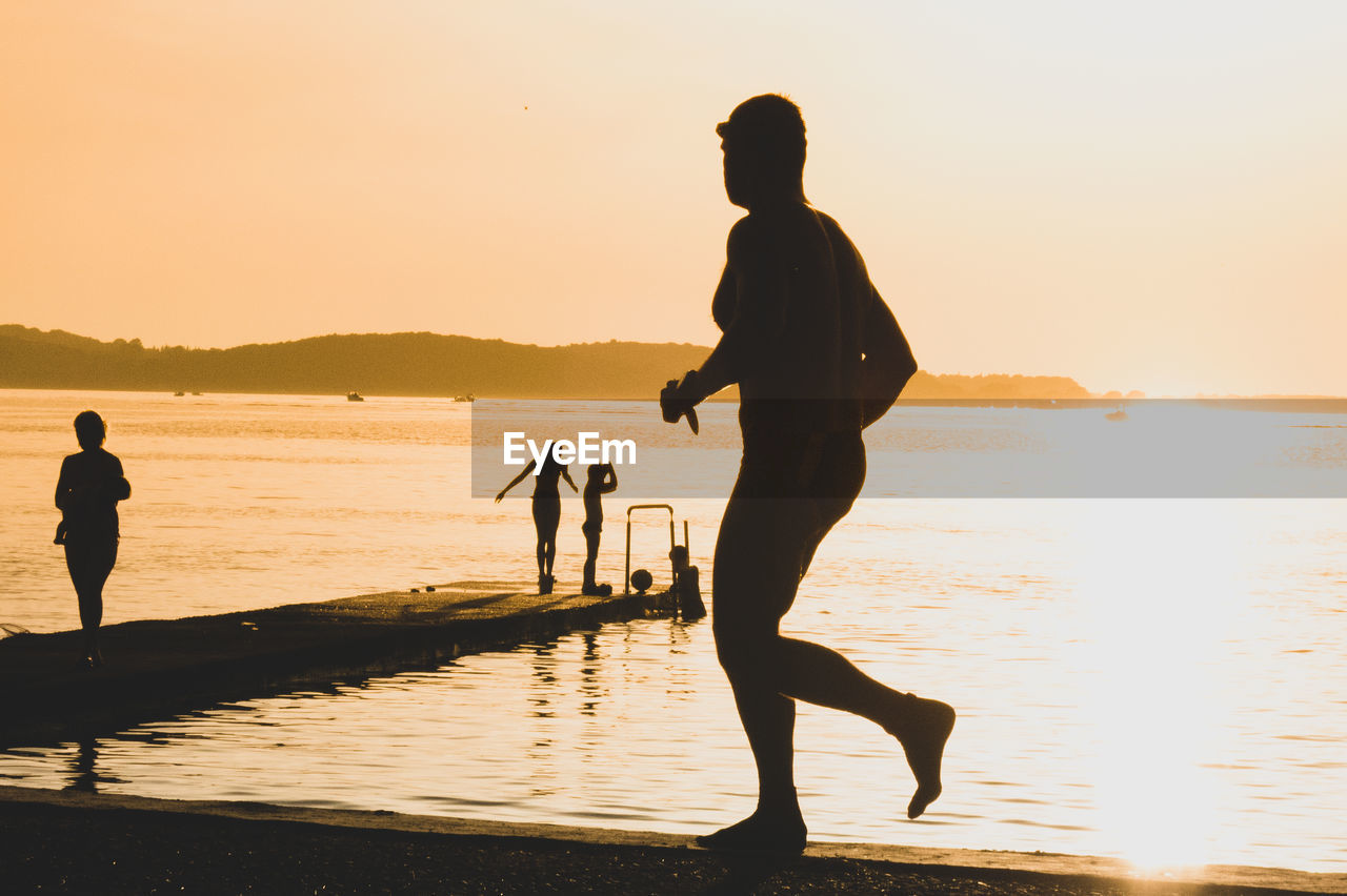 Side View Of Man Running Against Sea During Sunset