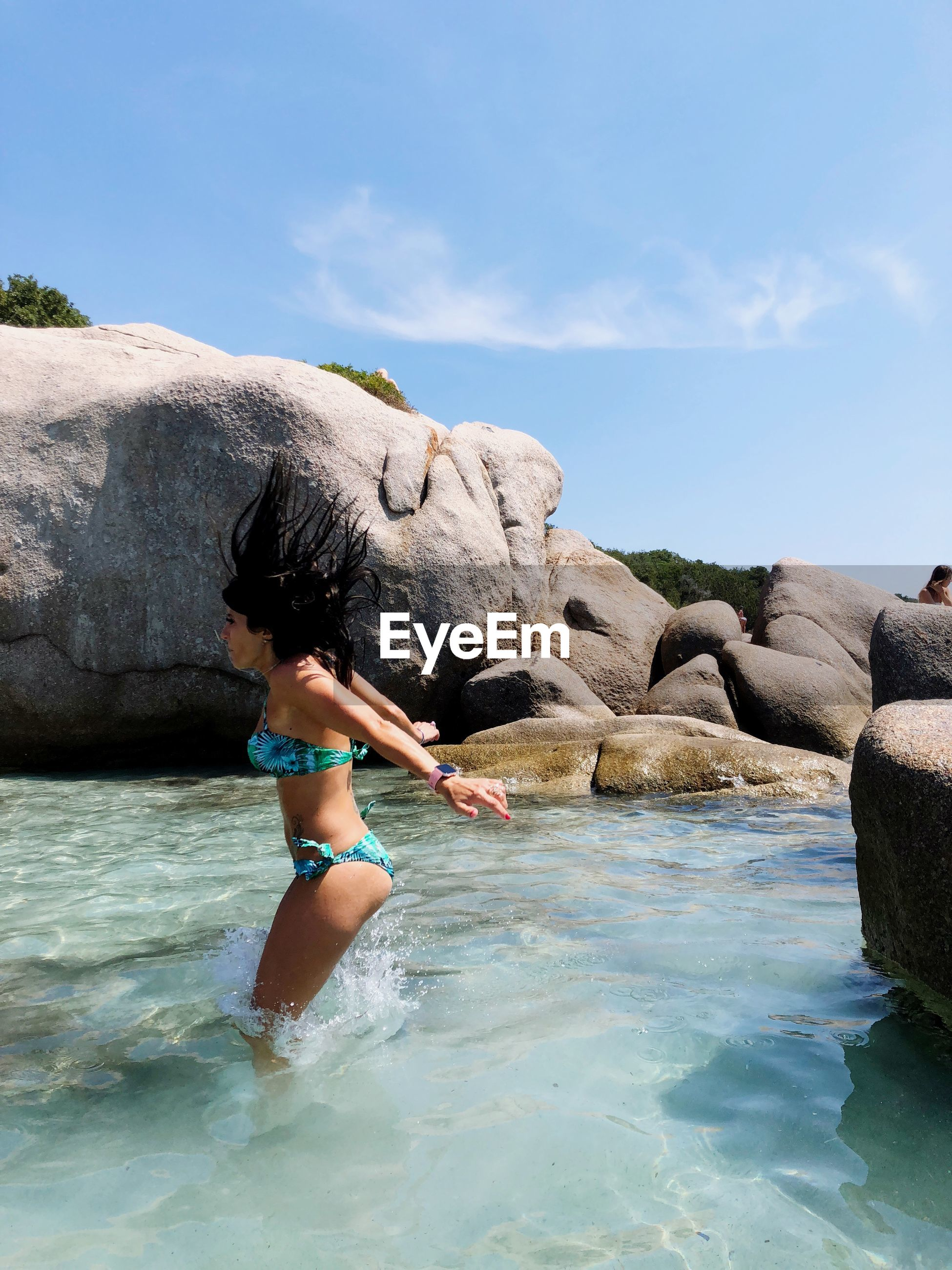 Side view of woman jumping into sea by rocks