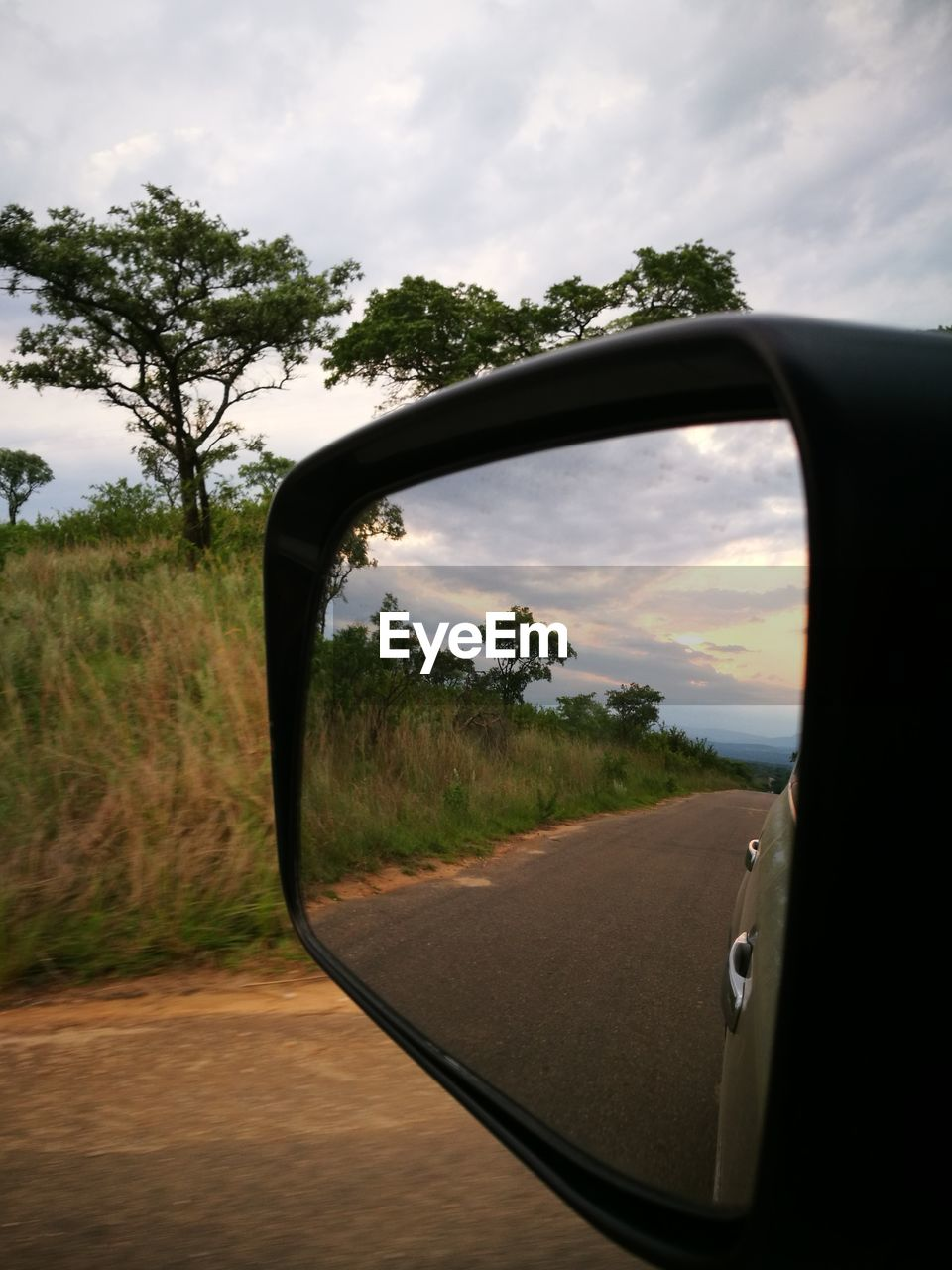 sky, side-view mirror, tree, cloud - sky, mode of transportation, land vehicle, car, nature, motor vehicle, transportation, sunset, plant, reflection, land, beauty in nature, no people, scenics - nature, glass - material, field, landscape, outdoors, vehicle mirror, road trip