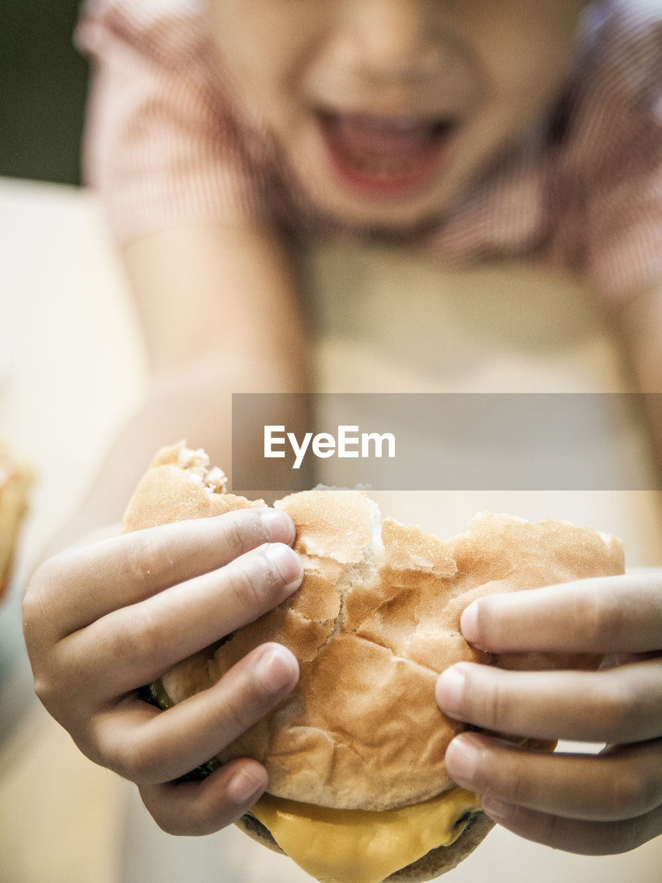High Angle View Of Boy Eating Burger At Table