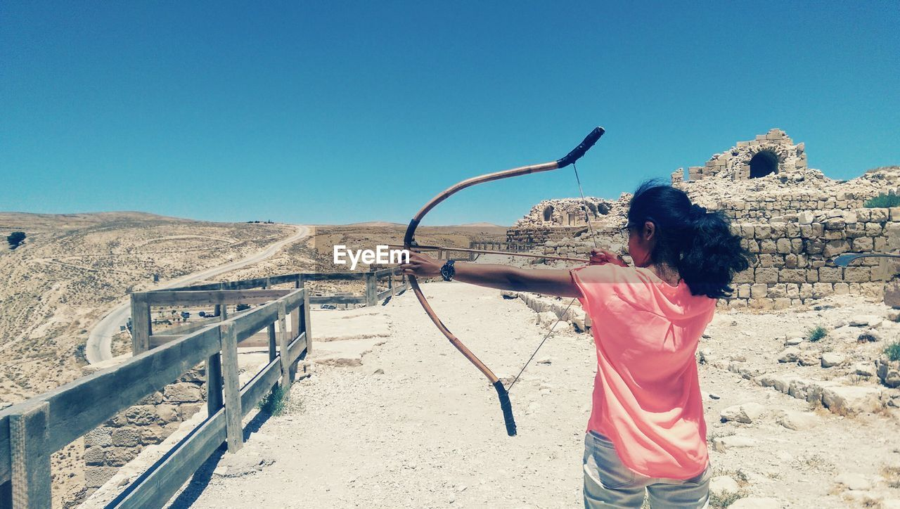 Rear View Of Woman Aiming With Bow And Arrow By Old Ruins Against Clear Sky