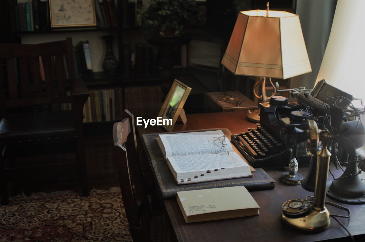 High Angle View Of Books With Vintage Telephone And Typewriter On Table