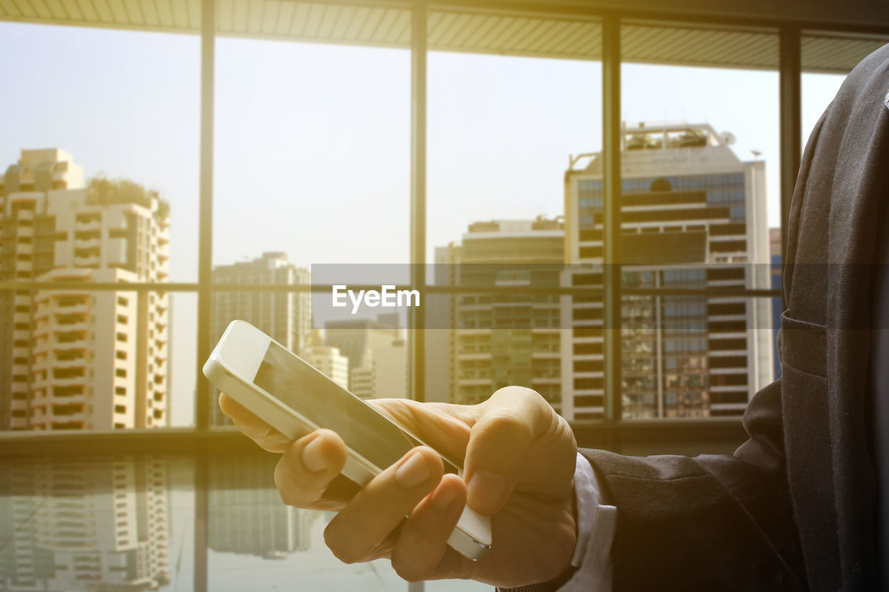 Cropped Image Of Businessman Using Mobile Phone In Office During Sunset