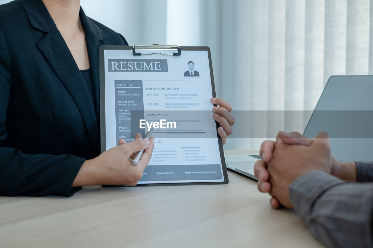Midsection of female manager showing resume to candidate at desk