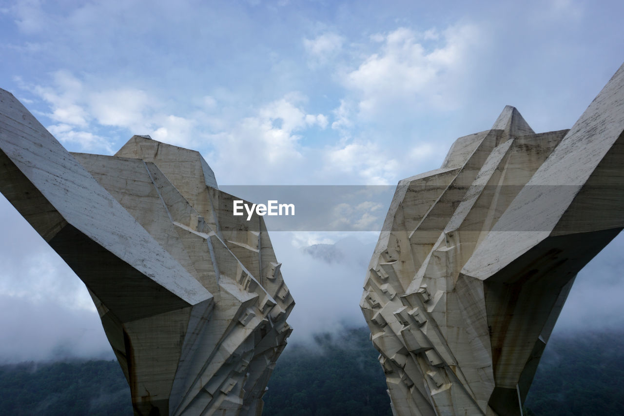 sky, cloud - sky, bridge - man made structure, bridge, low angle view, architecture, connection, day, built structure, no people, nature, outdoors, transportation, travel destinations, mountain, architectural column, tourism, art and craft
