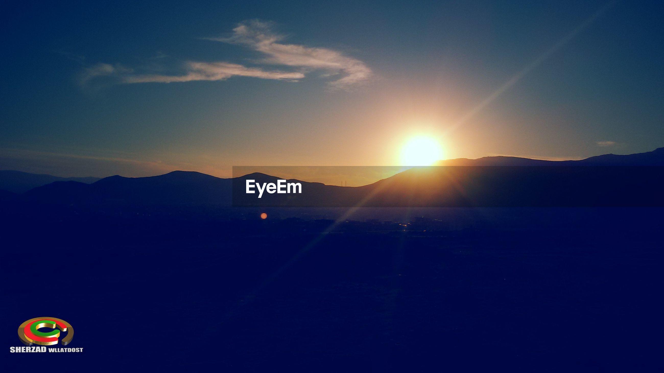 sunset, mountain, sun, scenics, beauty in nature, silhouette, sky, mountain range, tranquil scene, tranquility, nature, sunlight, orange color, idyllic, lens flare, landscape, outdoors, sunbeam, copy space, transportation