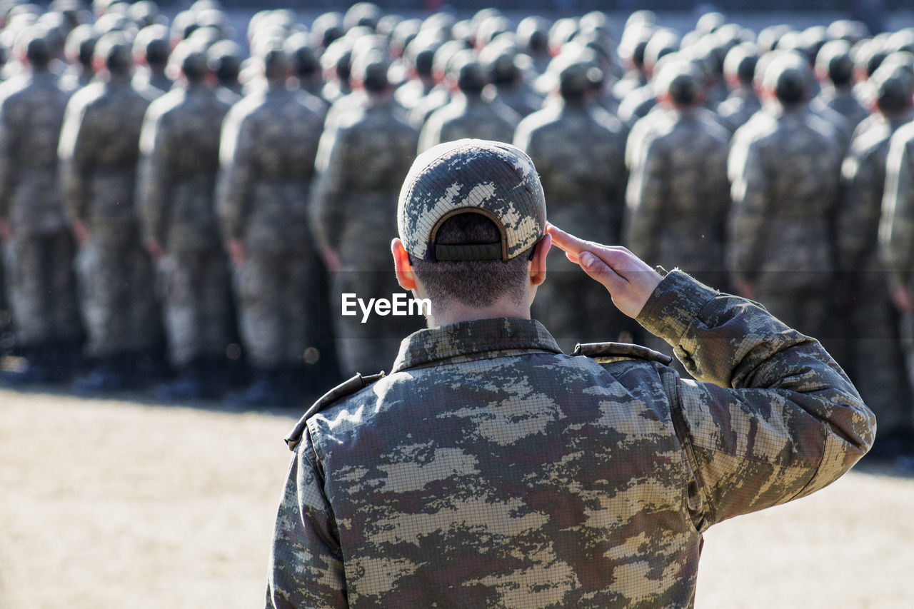 Rear view of soldier saluting outdoors