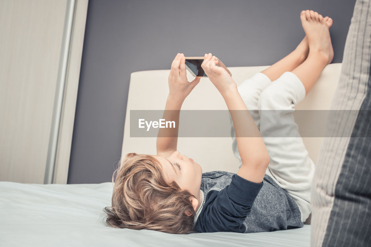 Boy Playing On Mobile While Lying On Bed With Feet Up At Home
