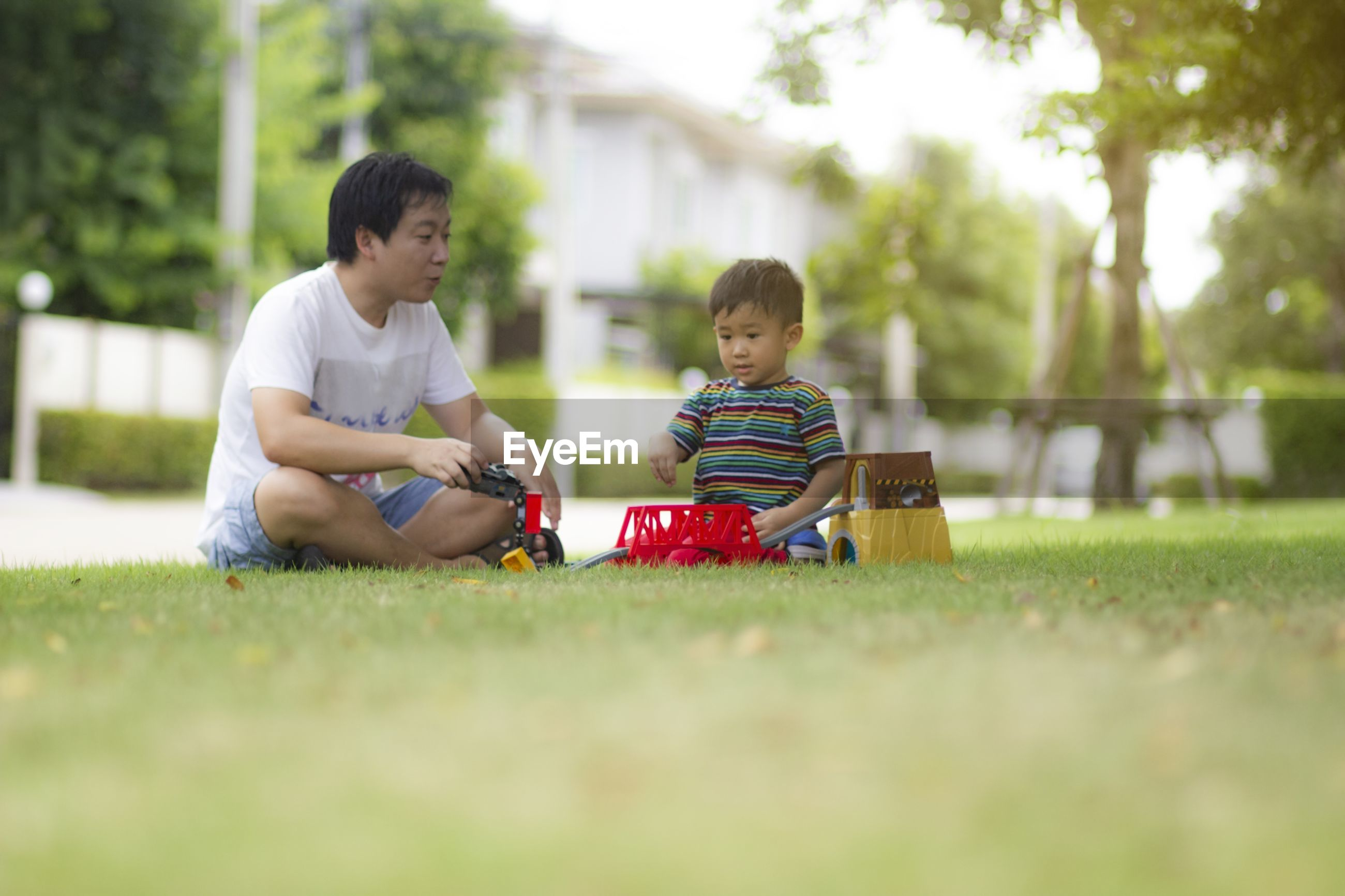 Father and son playing on grass in park