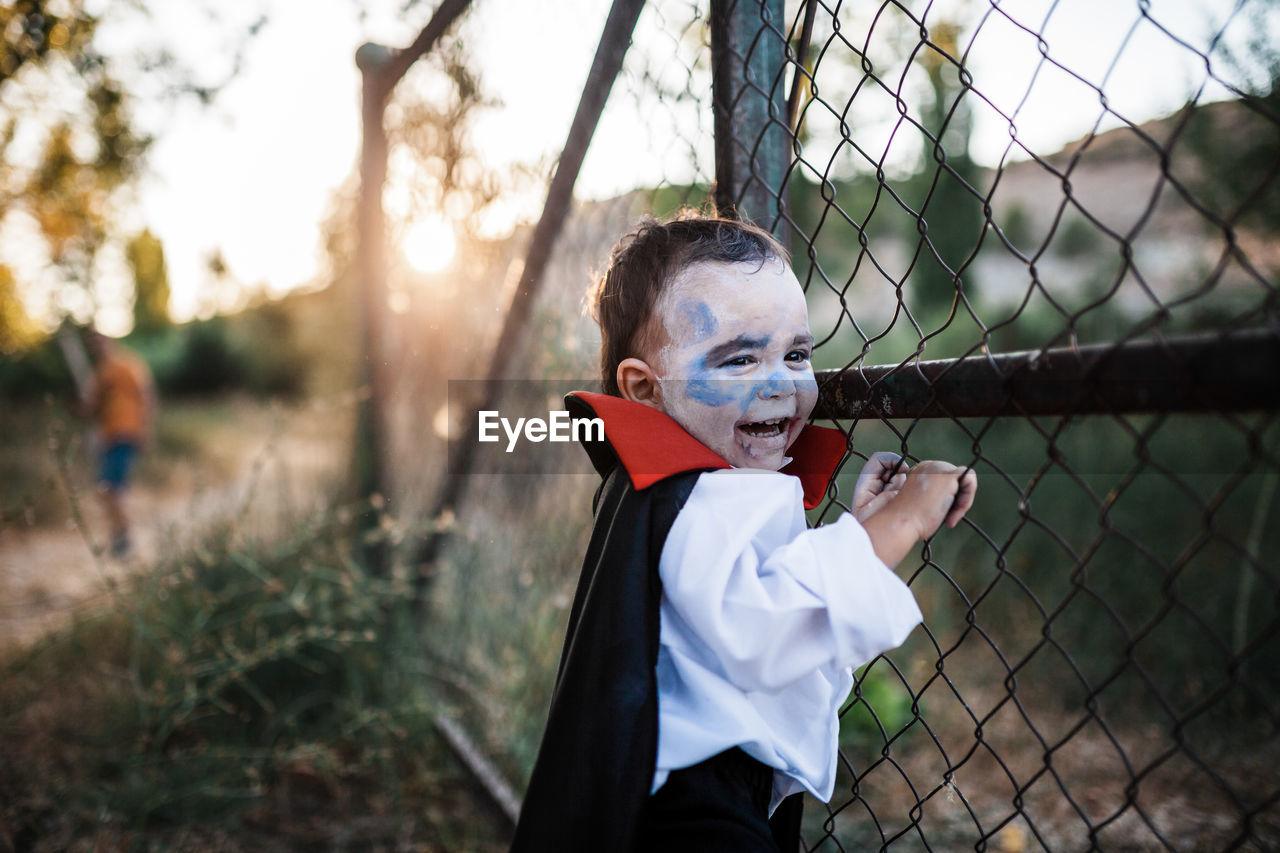 PORTRAIT OF BOY WEARING SUNGLASSES ON FIELD