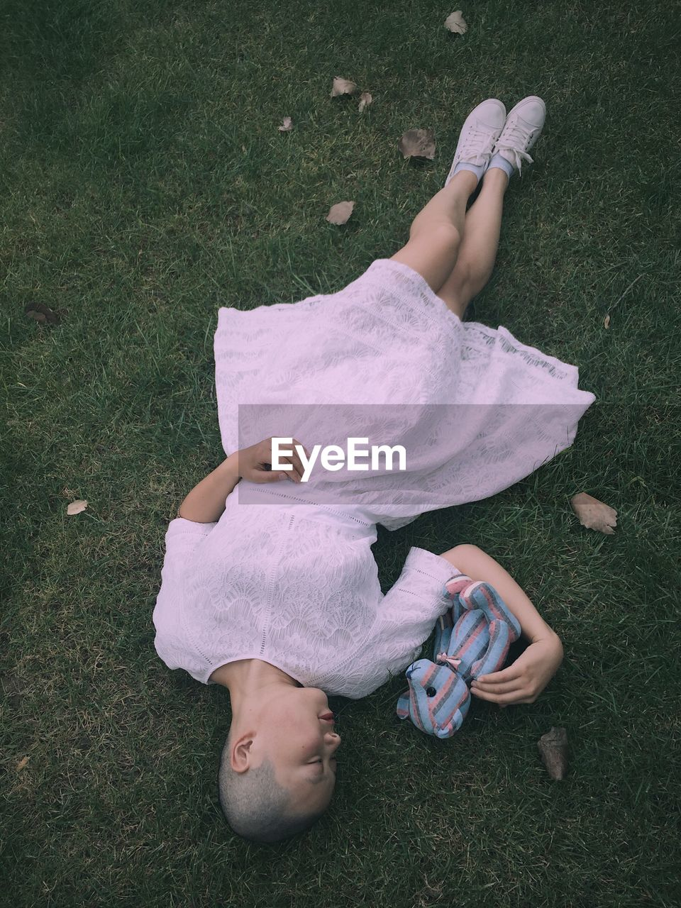 High Angle View Of Girl Lying On Grassy Field