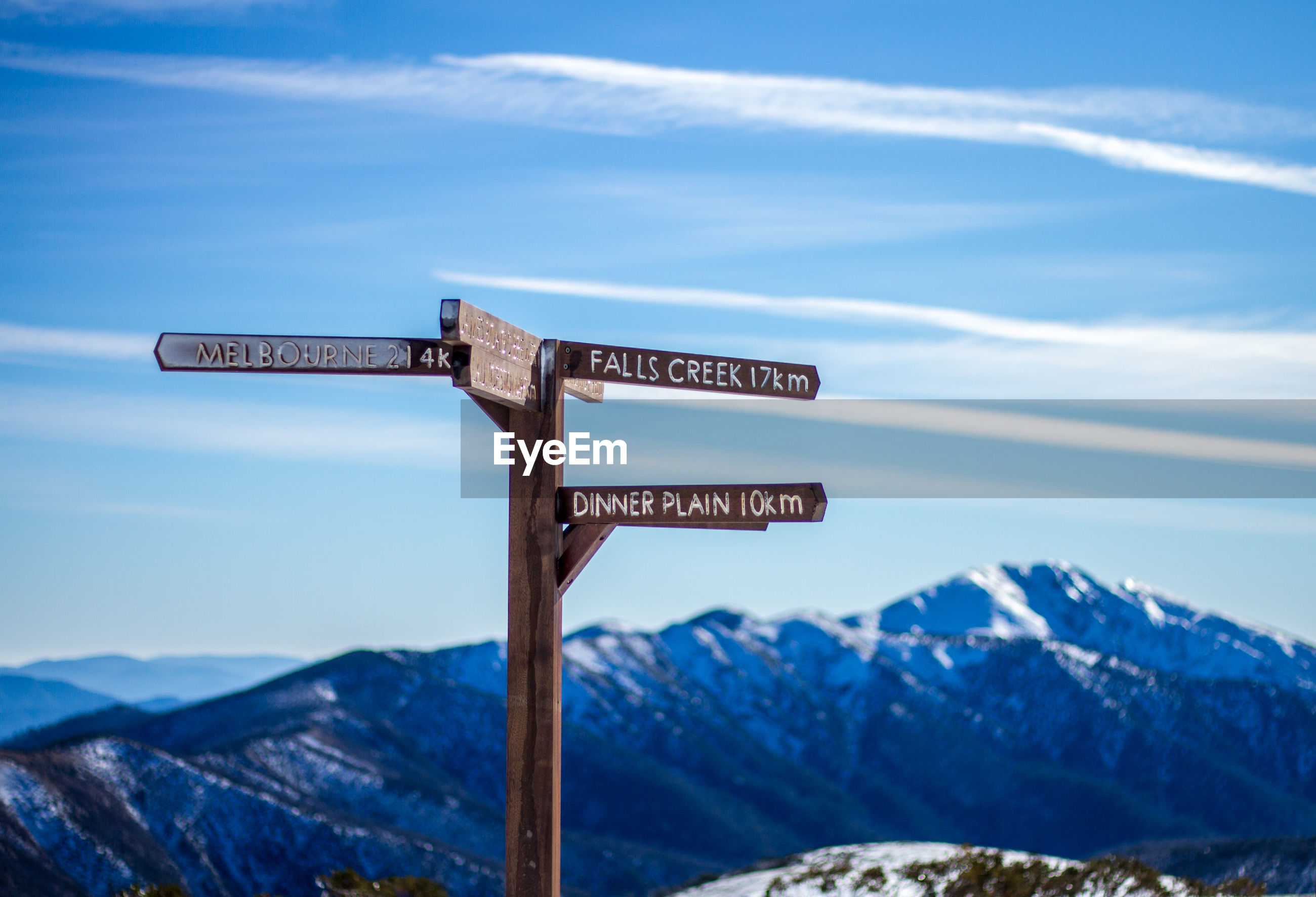 Information sign on snowcapped mountains against sky