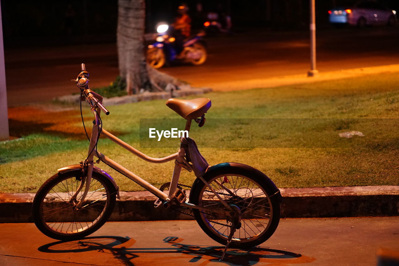 Bicycle Parked On Footpath At Night