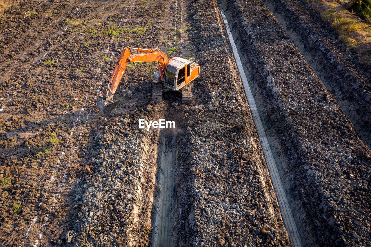 High angle view backhoe is dingging the groove garden and agricultural area evening time in thailand