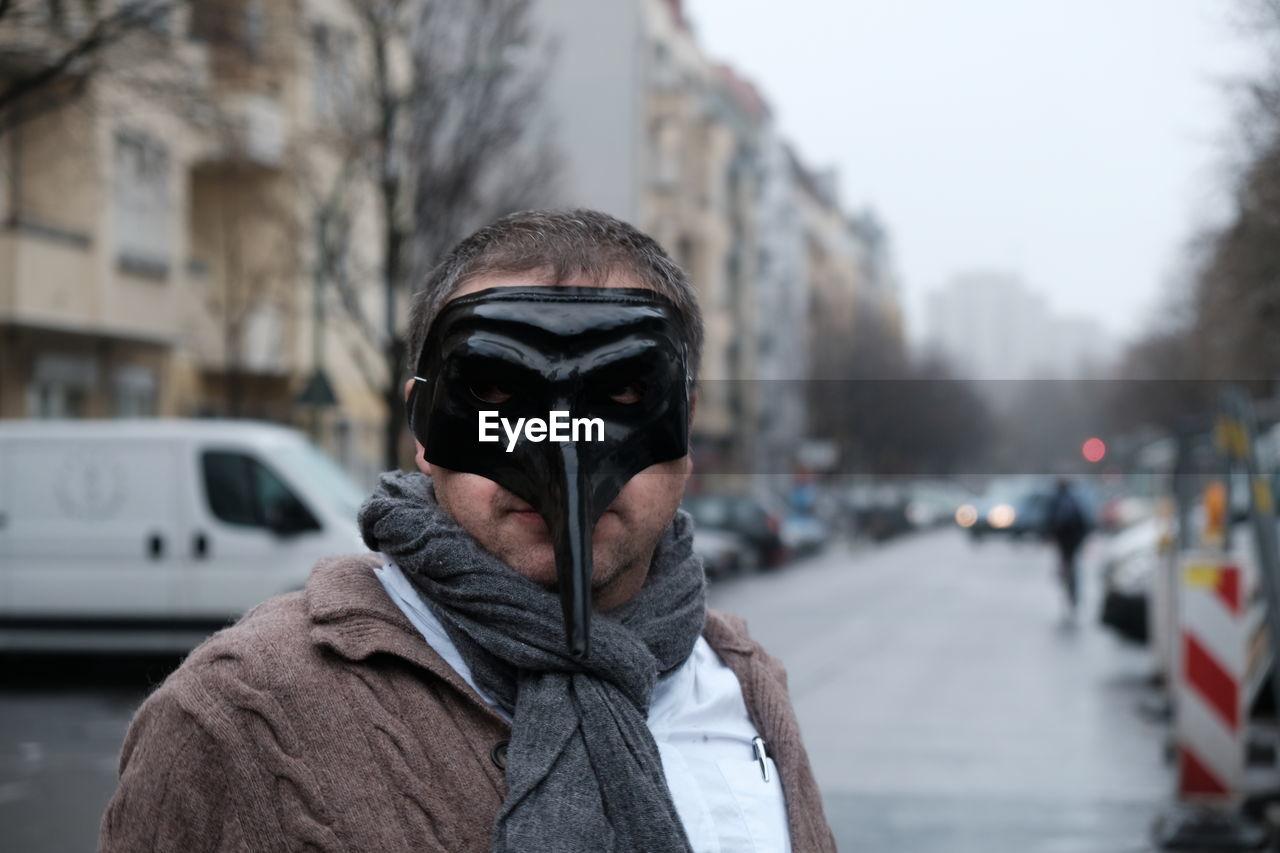 Portrait of man wearing mask on street in city