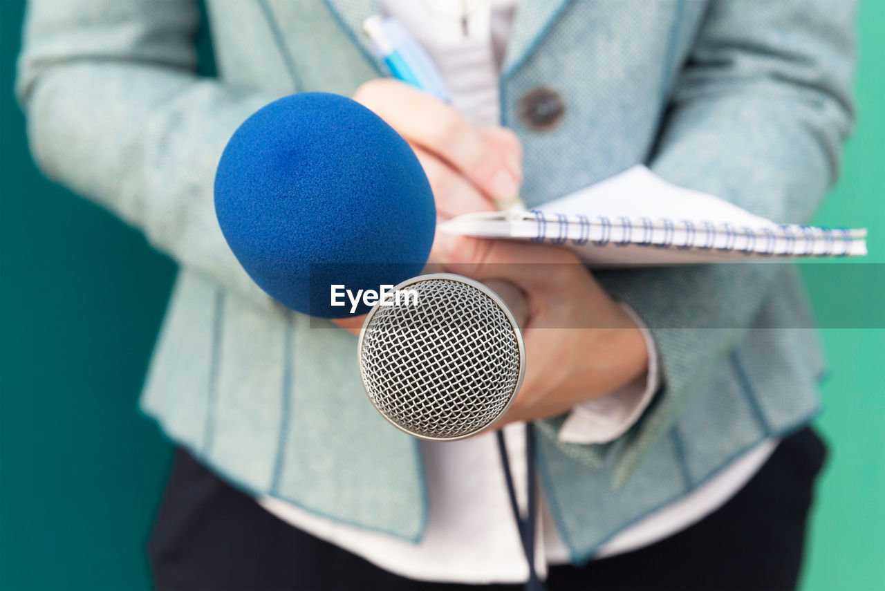 Midsection Of Female Journalist Holding Microphone