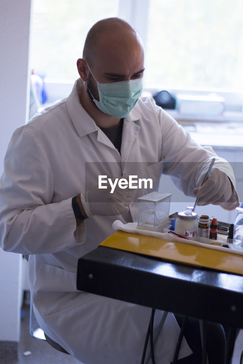 Doctor Working At Table In Laboratory