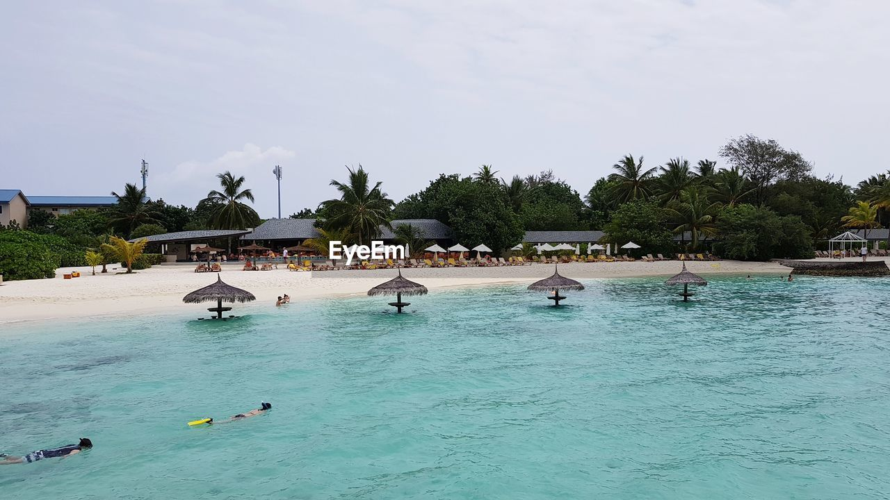 PEOPLE SWIMMING IN POOL AT BEACH