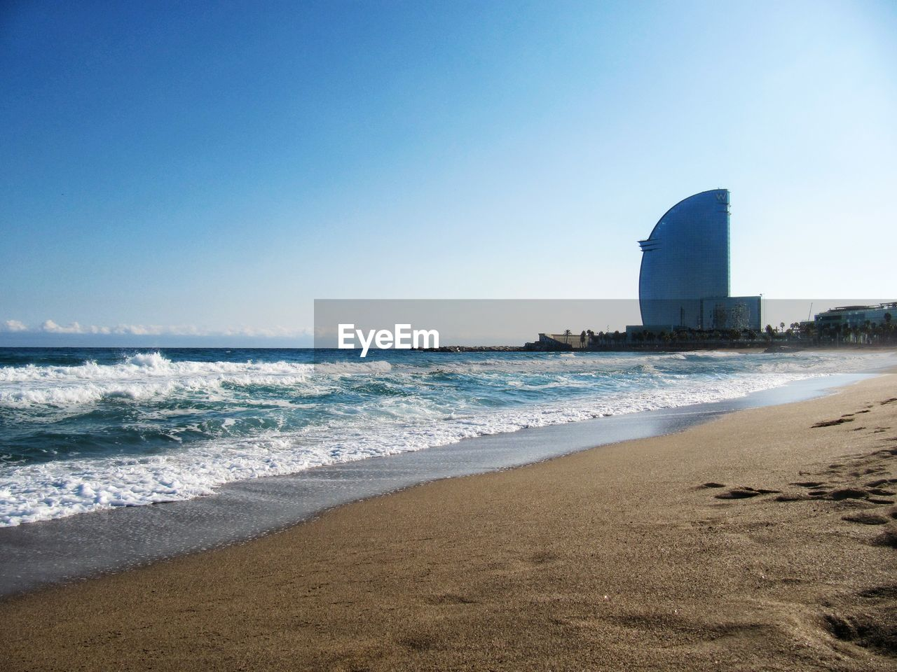 sea, beach, wave, built structure, clear sky, architecture, sand, water, building exterior, horizon over water, day, nature, no people, outdoors, lighthouse, beauty in nature, sky