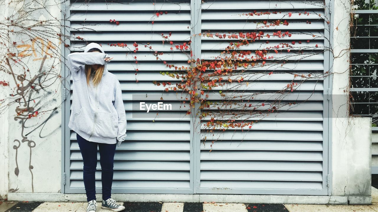 Full Length Of Girl Covering Face With Hand By Door