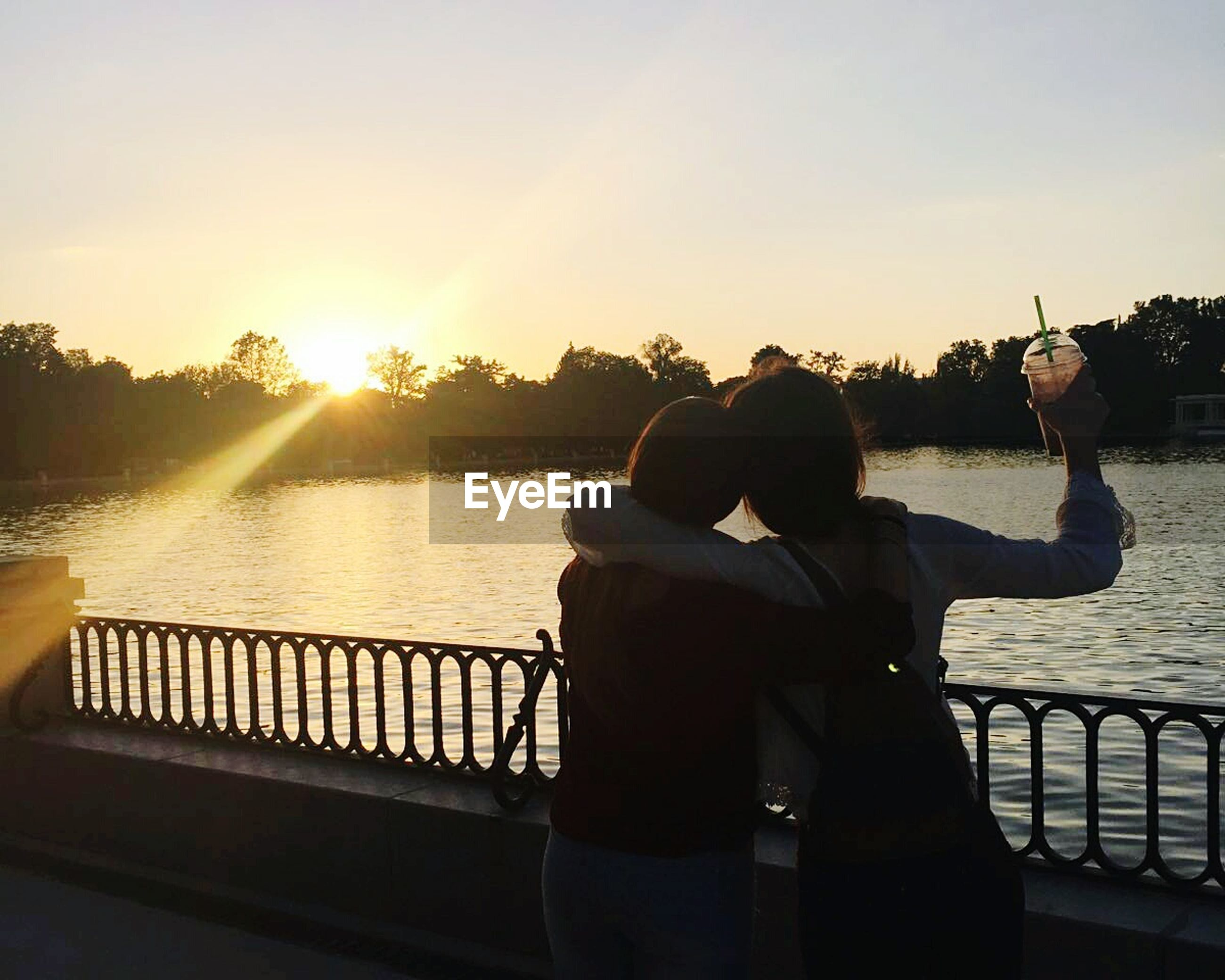 water, rear view, lifestyles, leisure activity, sunset, sun, railing, sitting, clear sky, lake, river, three quarter length, sunlight, standing, men, person, sky