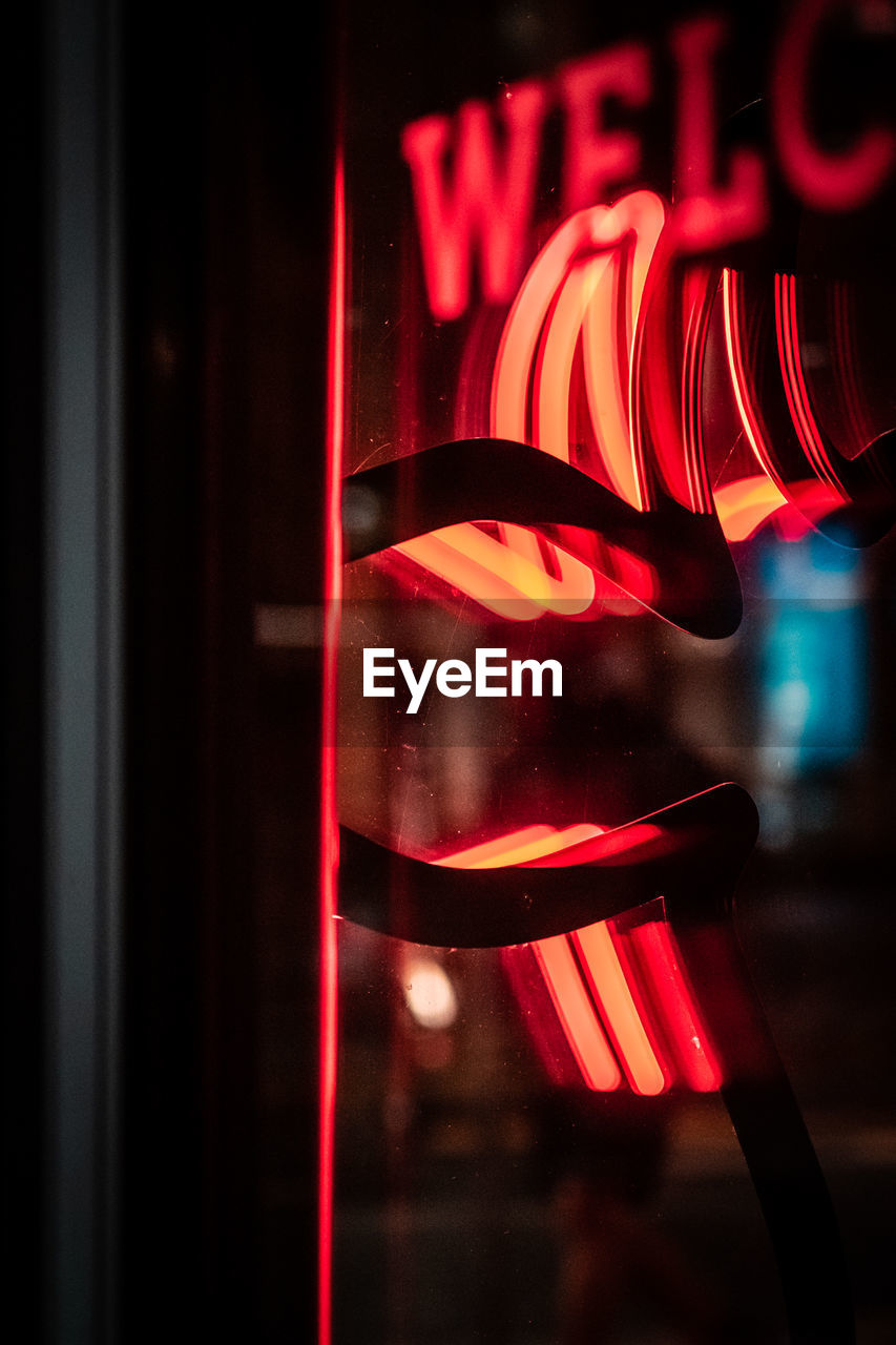 illuminated, red, no people, glowing, focus on foreground, indoors, glass - material, close-up, night, transparent, motion, lighting equipment, light - natural phenomenon, seat, neon, reflection, long exposure, window, striped, nightlife