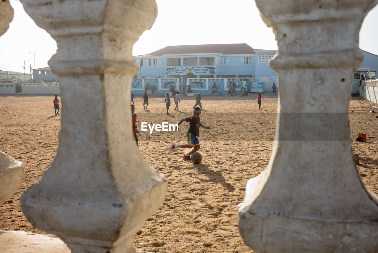 sand, real people, beach, architecture, playing, outdoors, day, leisure activity, built structure, sport, lifestyles, nature, sky, beach volleyball