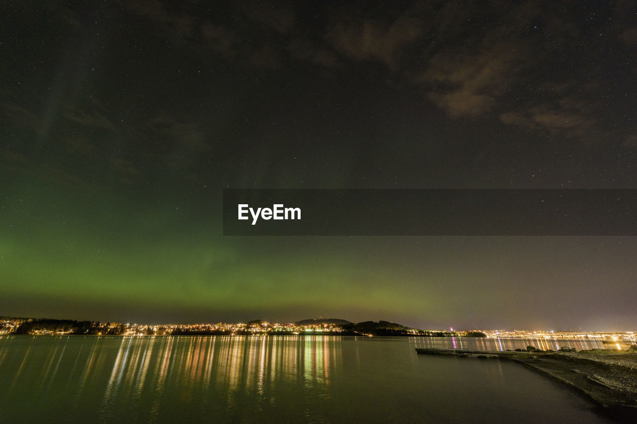 Aurora over  city night sky with water reflections