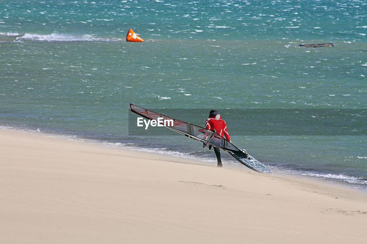 Man With Kiteboard At Beach