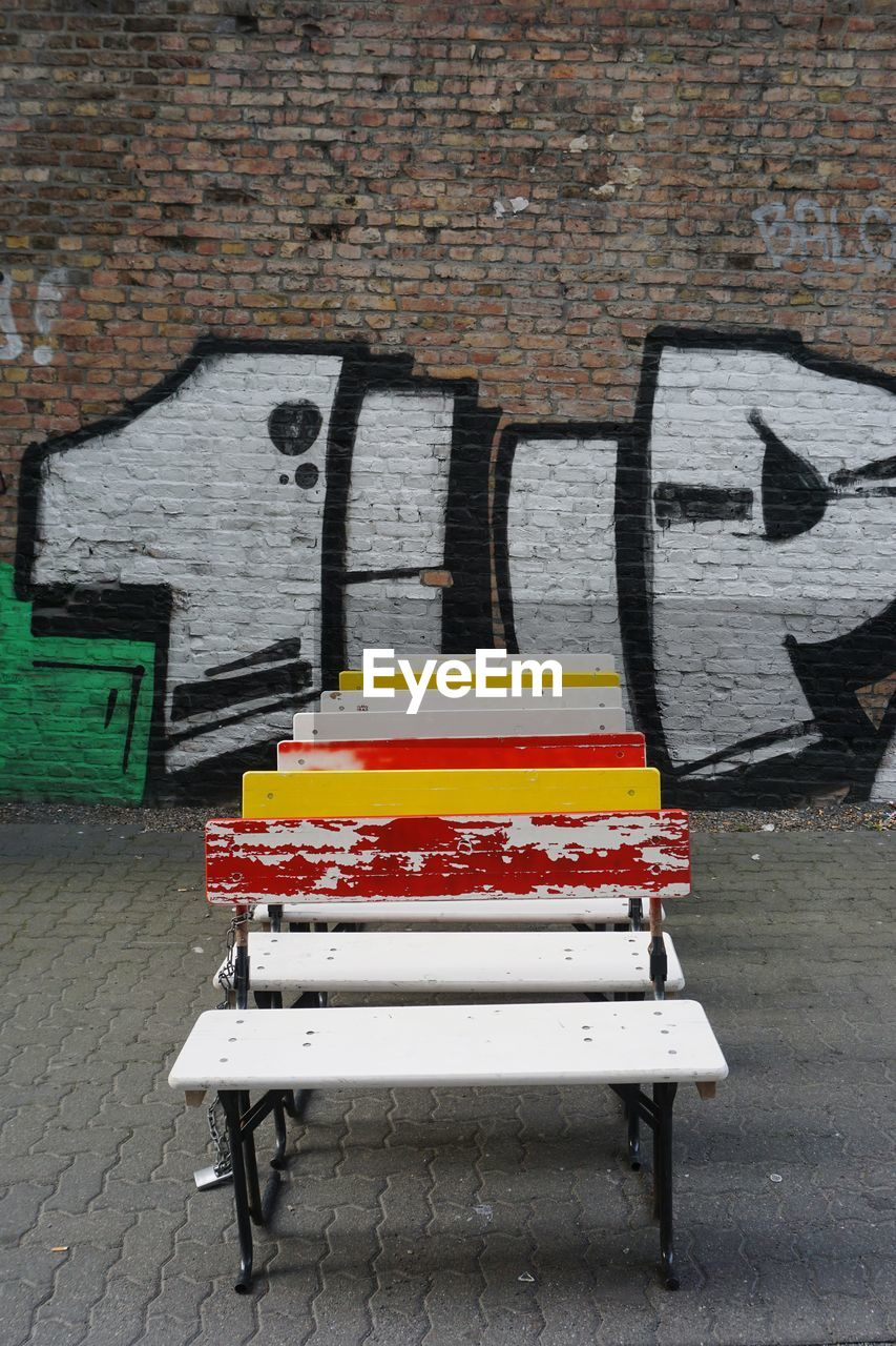 wall, wall - building feature, architecture, brick wall, brick, graffiti, building exterior, built structure, city, no people, seat, empty, bench, street, art and craft, footpath, day, multi colored, creativity, communication, mural