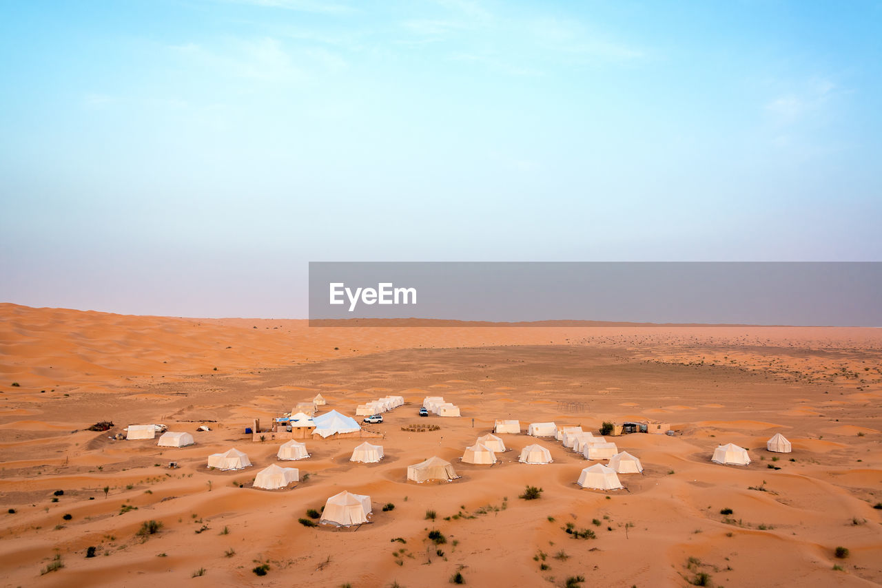 High angle view of tents at desert against blue sky
