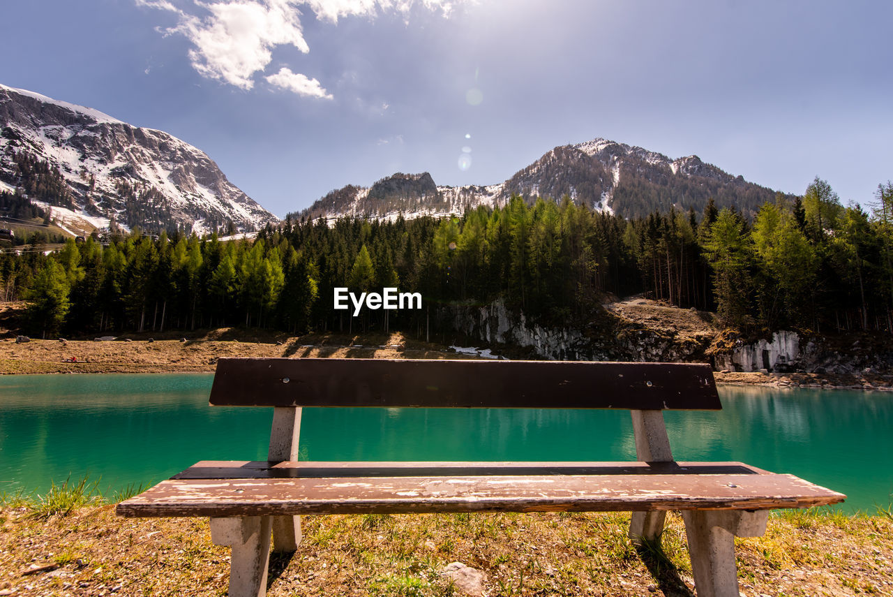 mountain, water, beauty in nature, lake, nature, sky, tranquility, tranquil scene, tree, bench, scenics - nature, seat, non-urban scene, idyllic, plant, day, mountain range, park, no people, outdoors, swimming pool, park bench
