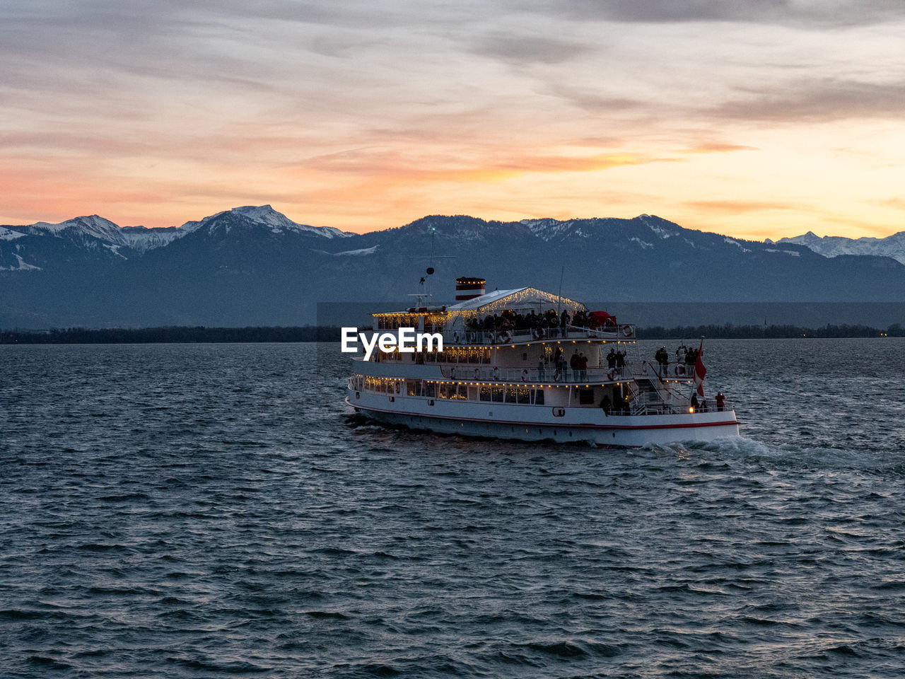 sky, mountain, nautical vessel, mode of transportation, water, transportation, beauty in nature, sunset, waterfront, cloud - sky, scenics - nature, mountain range, travel, sea, group of people, nature, sailing, real people, crowd, outdoors, passenger craft, snowcapped mountain