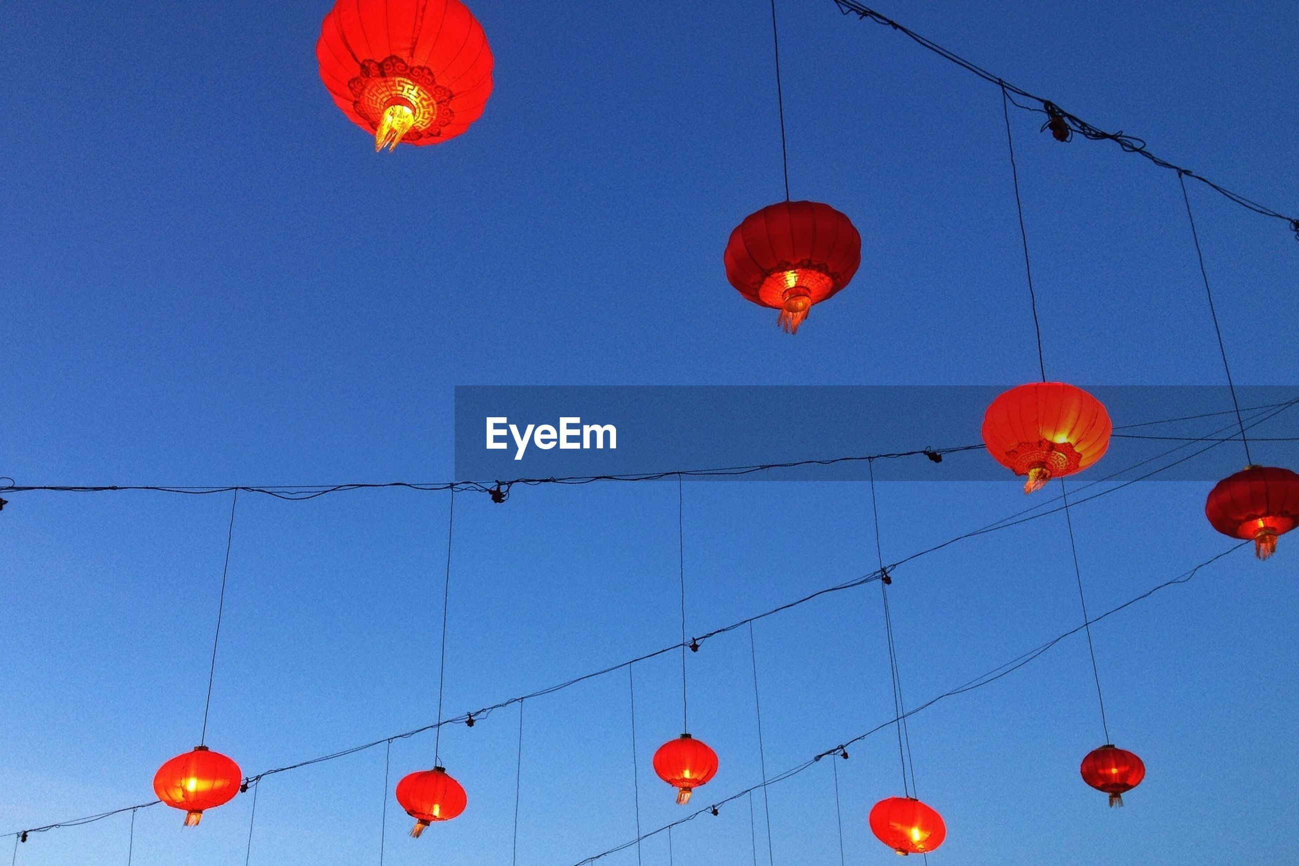 Low angle view of chinese lanterns hanging on cables against blue sky