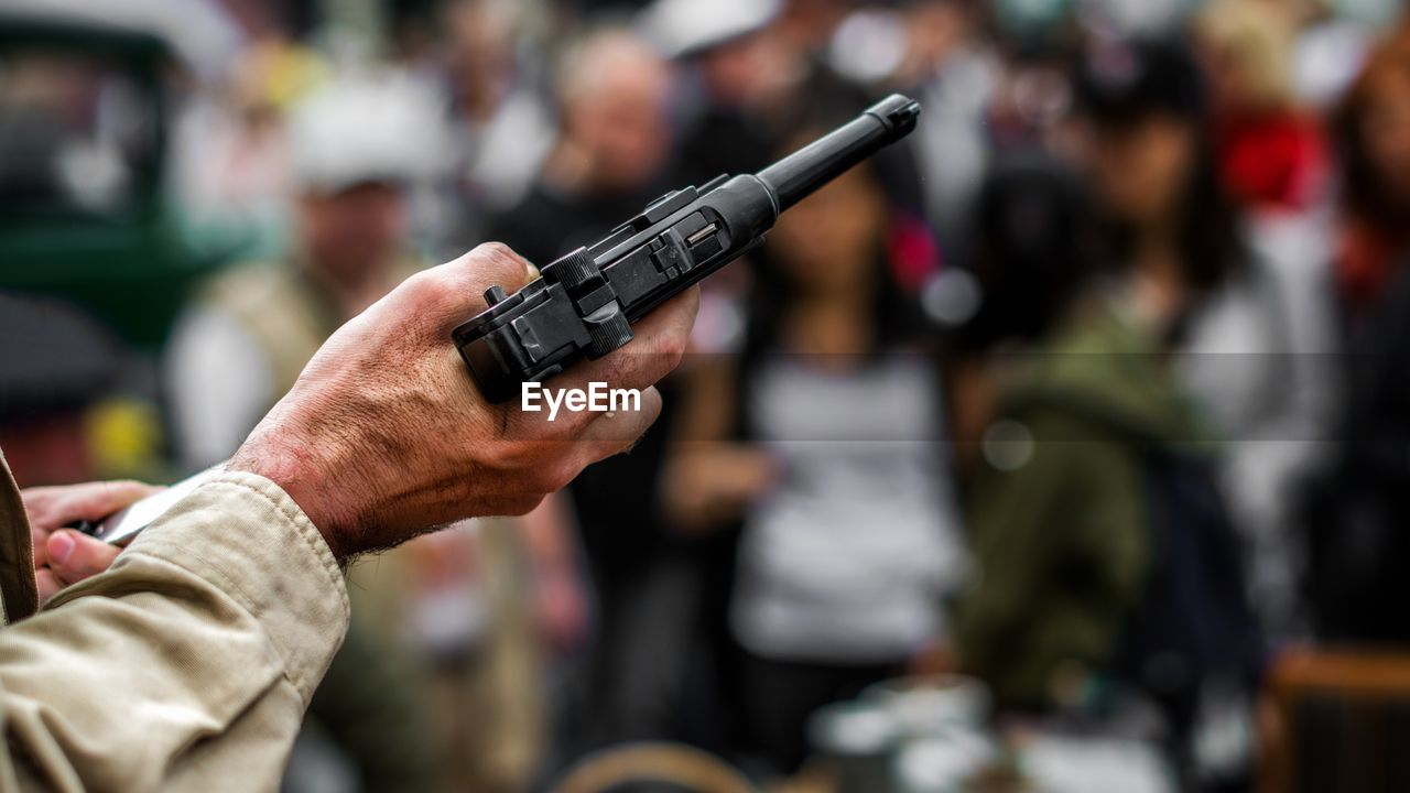 weapon, gun, focus on foreground, hand, human hand, holding, people, men, real people, shooting a weapon, human body part, handgun, incidental people, aiming, adult, day, clothing, close-up, military, rifle, aggression