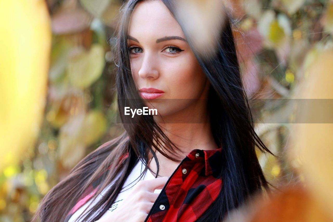 one person, long hair, beautiful woman, young adult, young women, real people, leisure activity, looking at camera, front view, outdoors, focus on foreground, day, lifestyles, portrait, standing, headshot, beauty, close-up, medium-length hair, nature, tree, people