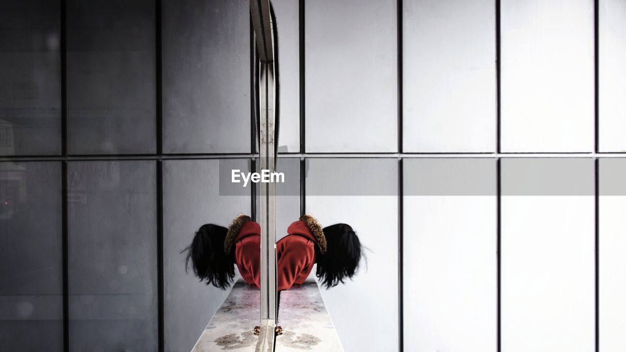Side View Of Woman Leaning With Reflection On Glass