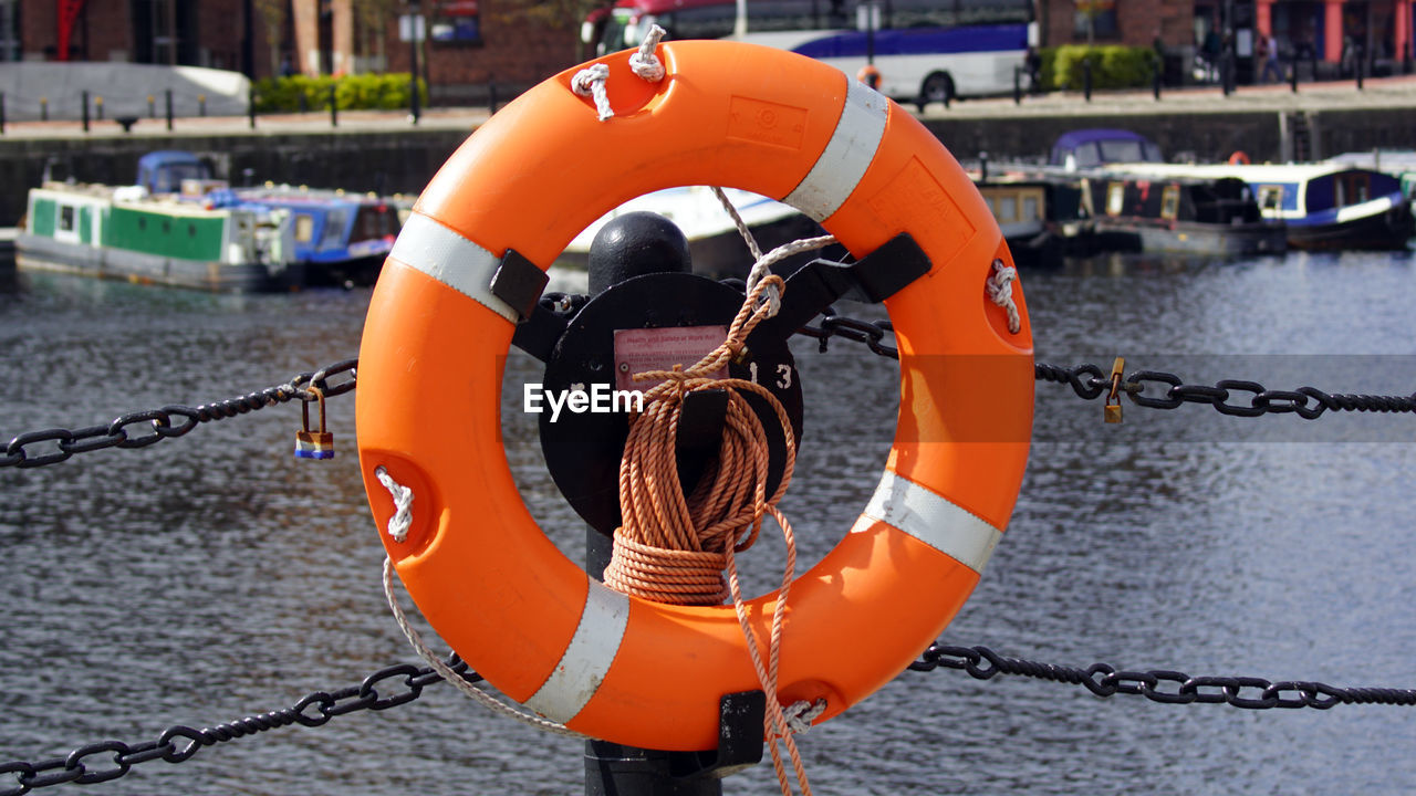 orange color, water, life belt, security, nautical vessel, safety, protection, rope, transportation, no people, mode of transportation, focus on foreground, day, buoy, harbor, hanging, chain, close-up, nature, outdoors, inflatable