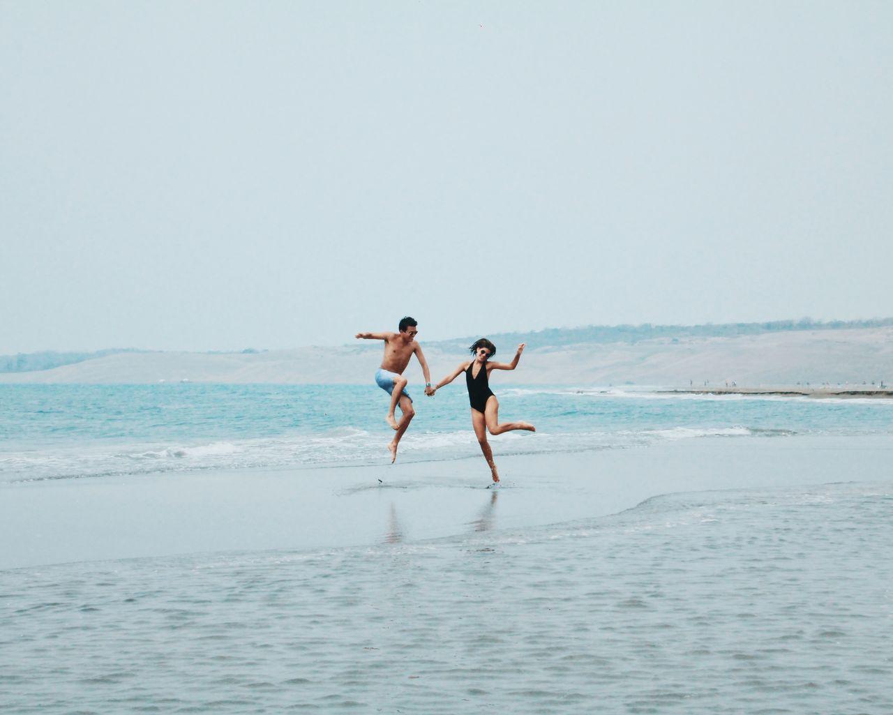 Friends On Beach Against Clear Sky