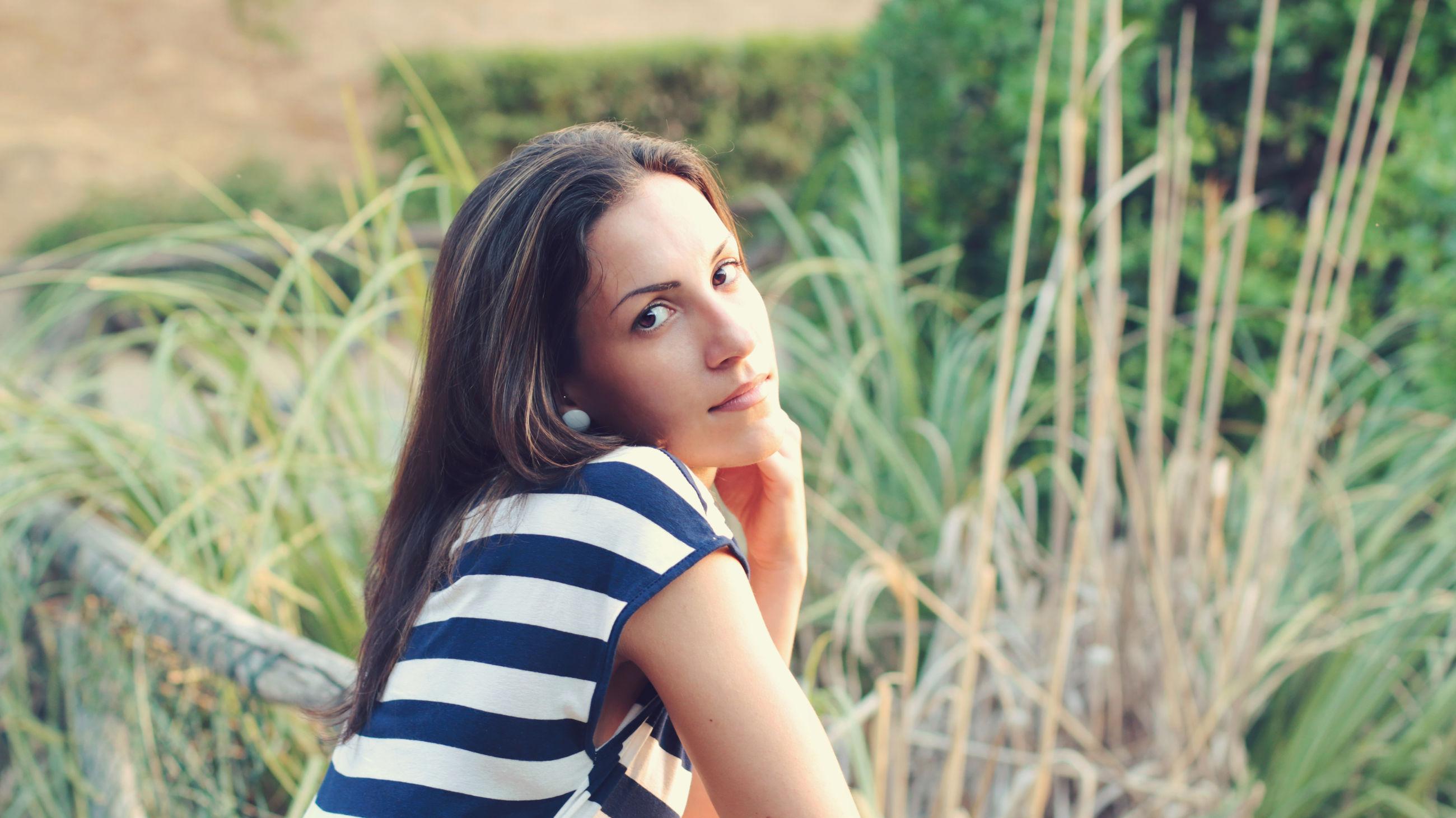 Portrait of young woman against plants at park