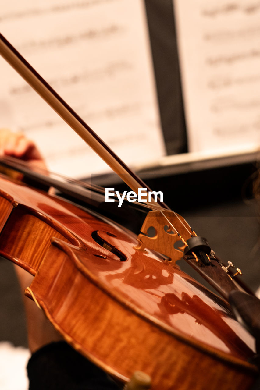 Midsection of person playing violin during orchestra