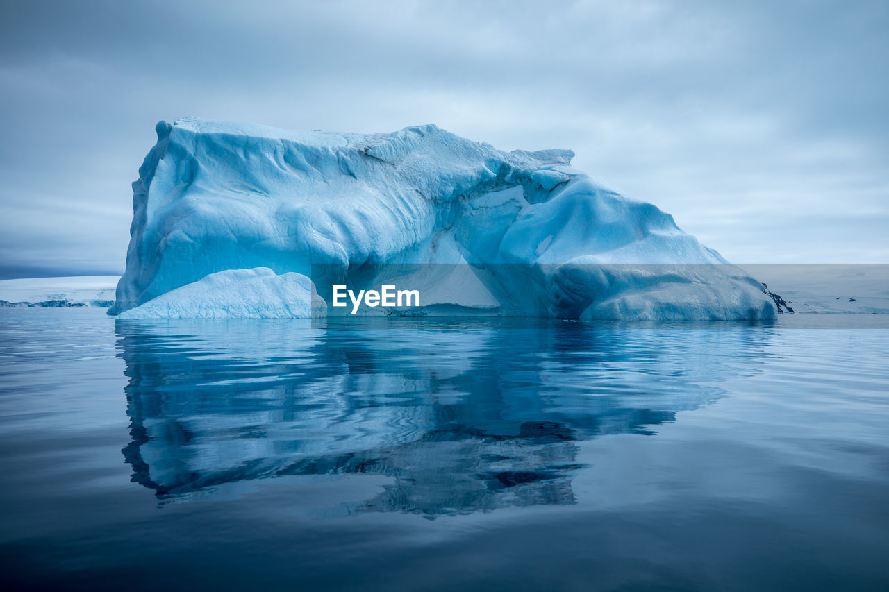 Scenic View Of Ice Berg In Lake Against Sky