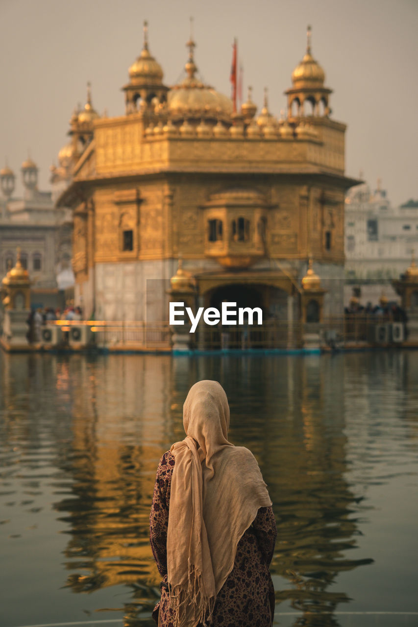Rear view of woman on the river against the golden temple